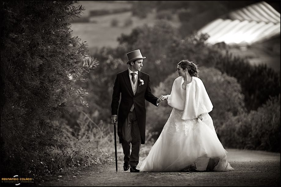 Bride and groom walking hand in hand in a black and white photography. He use a tall hat and a cane.