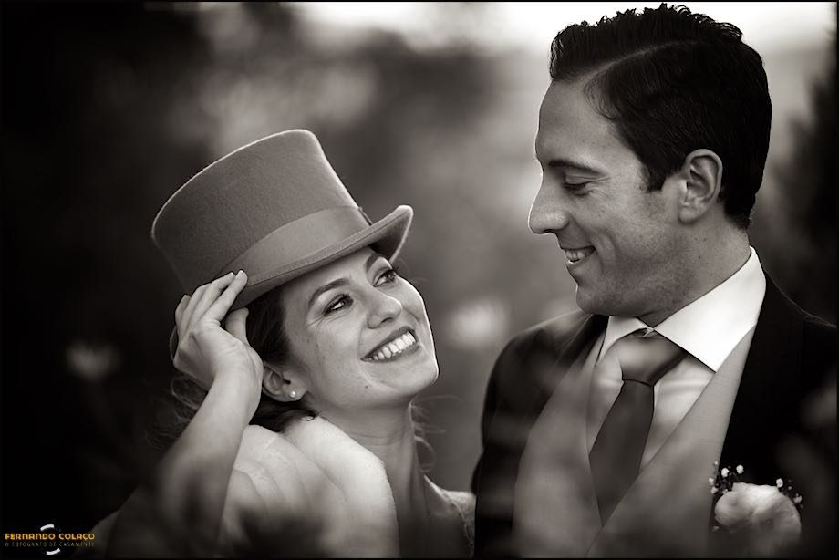 Black and white photography from a bride with a hat near the groom.