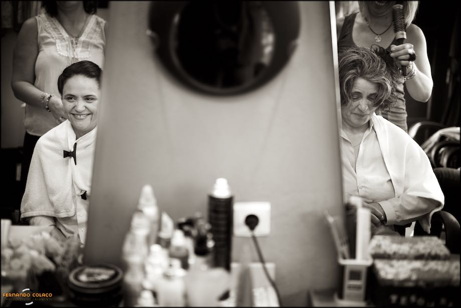 Bride and her mother in the mirror, at the hairdresser.