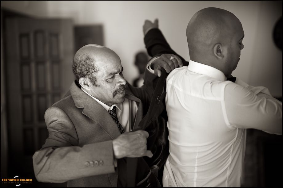 Father of the groom helping him dressing the coat, for the wedding ceremony.