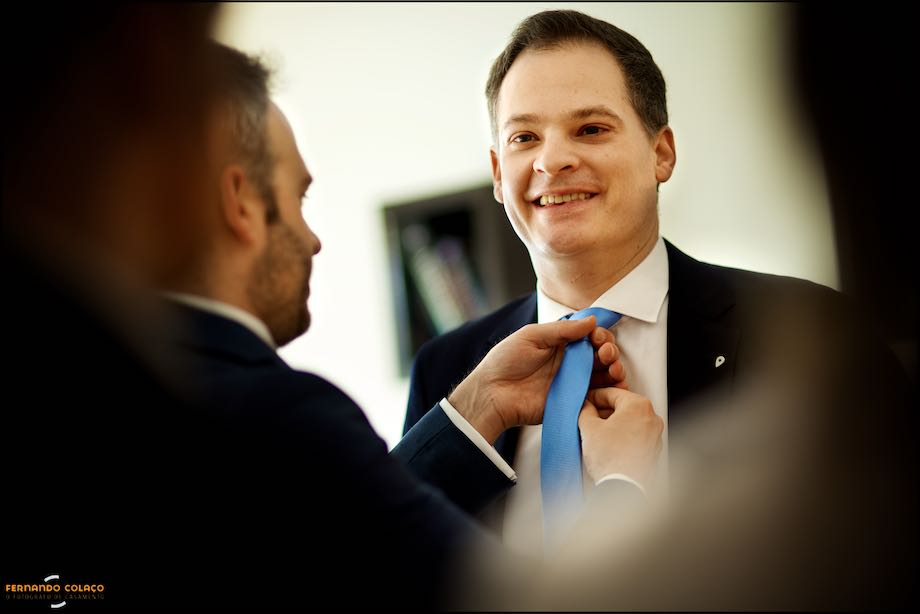 Groom with guest, fine tuning the necktie.