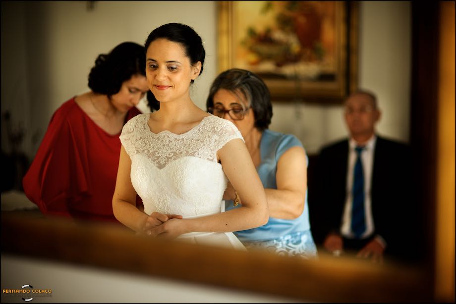Bride, in a mirror, tightening the dress, by mother and sister and father in the back.