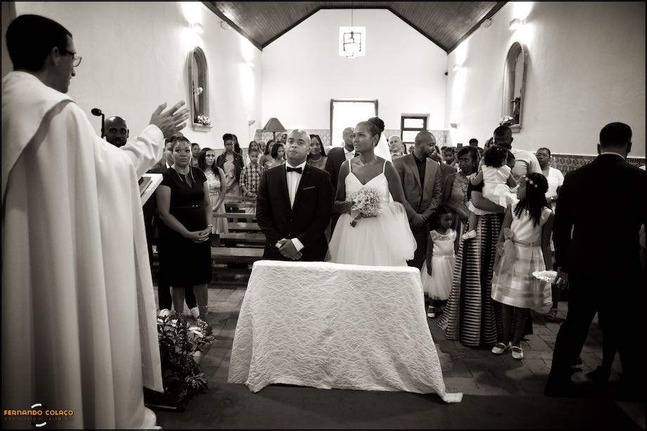 View inside the church with the couple in the front at the wedding ceremony.