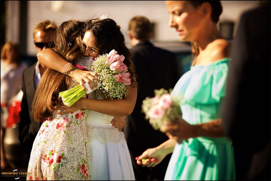 Bride, with the bouquet in her hand, hugging a woman guest with another in the right.