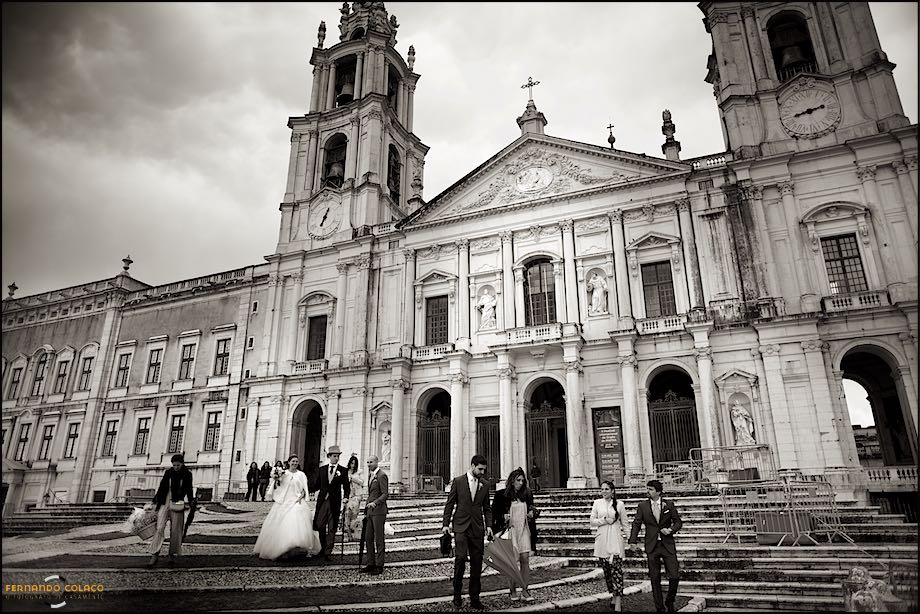 Bride and groom and guests coming down the stairs with the Basilica of Mafra in the back.