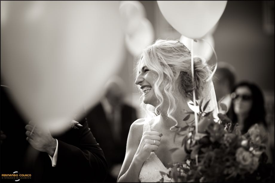 Bride laughing between balloons and guests.
