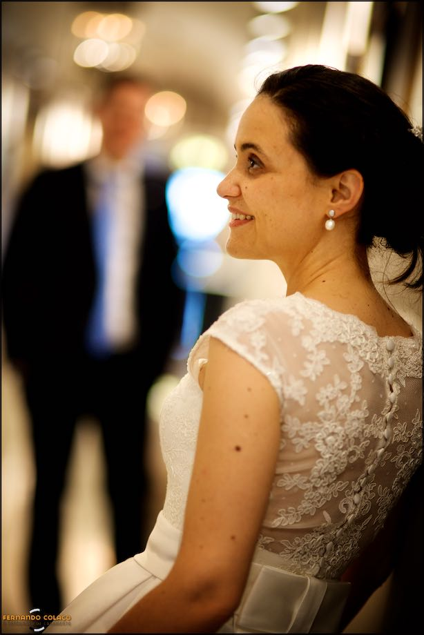 Bride in profile, leaning, with unfocused groom, ahead, in the wedding session.