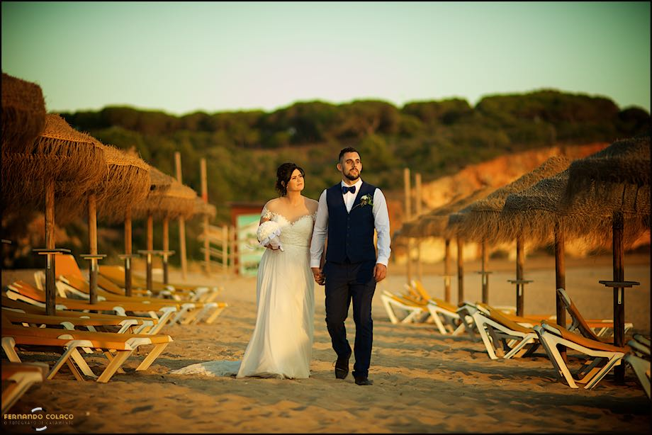 Couple, after the marriage, walking on a beach in Algarve.
