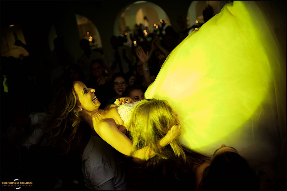 Bride on guests shoulders under yellow light, at wedding party.