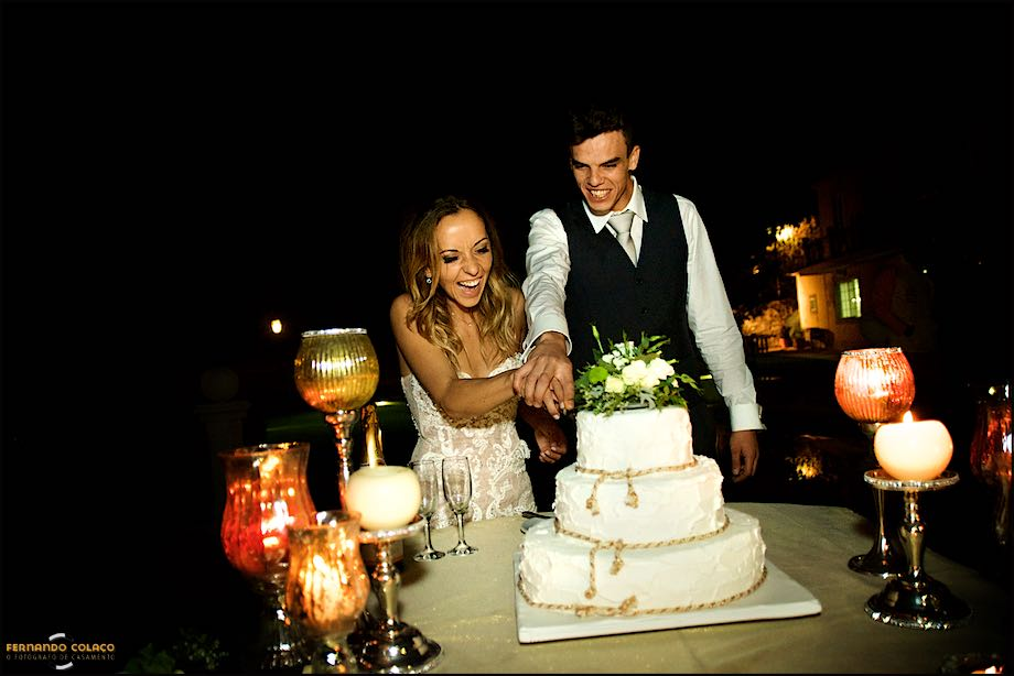 Bride and groom, together, cutting the wedding cake.